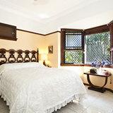 Красивый интерьер спальни с окнами из дерева
