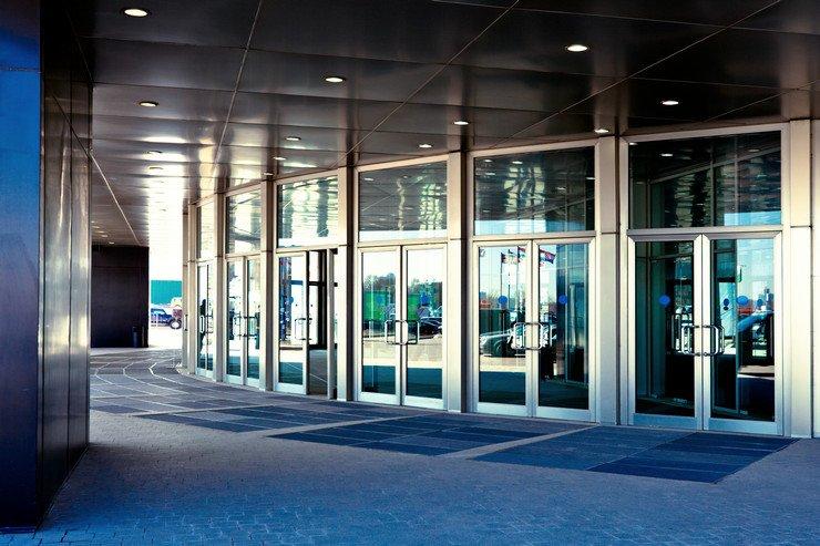 Остекленная полукругом дверная группа современного бизнес-центра