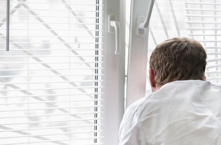 Мужчина смотрит в приоткрытое окно